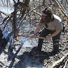 PETE BANNAN-DIGITAL FIRST MEDIA Hibernia Park ranger Vicki Rhine uses a axe to get at hidden fire in burned logs.