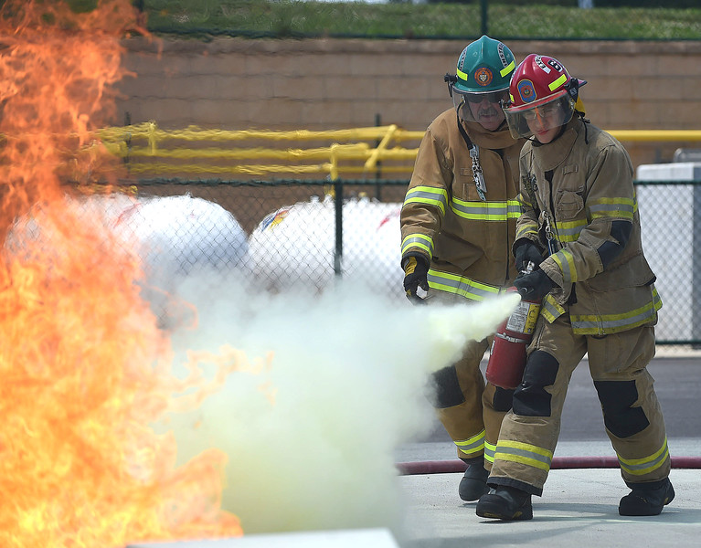 PETE BANNAN-DIGItAL FIRST MEDIA   Kimberton junior firefighter, Ira Deger extinguishes a training funder the supervision of Instructor Jim Reagan at the Chester County Emergency Services training center Monday afternoon as part of the junior public safety camp.