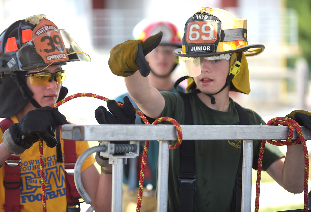 . PETE BANNAN  DIGITAL FIRST MEDIA  Lucas Richardson of Twin Valley Fire  Company,right, helps Sam Curdo of W. Bradford Fire Cmpany as they tie the clove hitch knot Chester County Department of Emergency Services� Junior Public Safety Camp Olympics Thursday at the Chester County Public Safety Training Campus, Tactical Village in S. Coatesville. The Junior Olympics takes the skills that the students, aged 14 to 17, have spent a week learning and puts them to practical use in various scenarios.