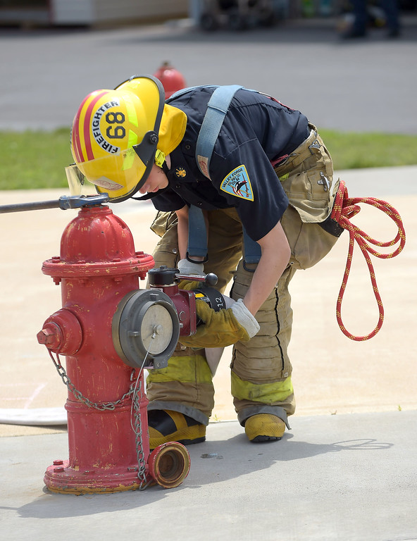 . PETE BANNAN  DIGITAL FIRST MEDIA   Elijah ROmano of Valley Forge Fire Company attaches a hose to the hydrent during Chester County Department of Emergency Services� Junior Public Safety Camp Olympics Thursday at the Chester County Public Safety Training Campus, Tactical Village in S. Coatesville  The Junior Olympics takes the skills that the students, aged 14 to 17, have spent a week learning and puts them to practical use in various scenarios.