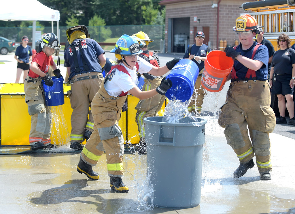 . Junior firefighters take part in the buck brigade component of  Chester County Department of Emergency Services� Junior Public Safety Camp Olympics Thursday at the Chester County Public Safety Training Campus, Tactical Village in S. Coatesville. The buckets had holes drilled in it to make the test more challenging.