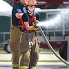 CHarles Ziegler of Wagontown Fire Company and Alexandra DiPaolo of the Glen Moore Fire Company advance a hose as part of  Chester County Department of Emergency Services' Junior Public Safety Camp Olympics Thursday at the Chester County Public Safety Training Campus, Tactical Village in S. Coatesville. The test was to knock a ball, in the foreground, off a cone.