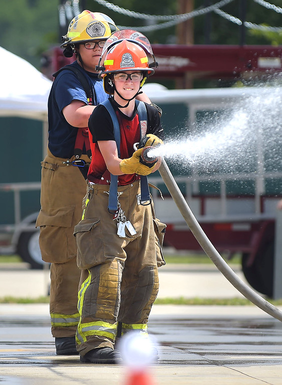 . CHarles Ziegler of Wagontown Fire Company and Alexandra DiPaolo of the Glen Moore Fire Company advance a hose as part of  Chester County Department of Emergency Services� Junior Public Safety Camp Olympics Thursday at the Chester County Public Safety Training Campus, Tactical Village in S. Coatesville. The test was to knock a ball, in the foreground, off a cone.