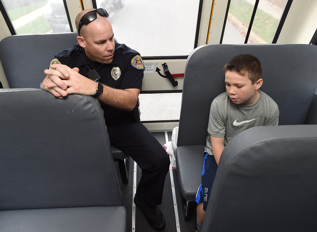 . PETE  BANNAN-DIGITAL FIRST MEDIA         Mary C. Howse Elementary student, Ryan Schellhammer speaks with West Whiteland Police Detective Jeff McCloskey who rode the school bus Wednesday to speak to the children about school bus safety as part of Operation Safe Stop.  Operation Safe Stop is part of National School Bus Safety Week,  a public awareness and enforcement effort to educate the motoring public that passing a stopped school bus, is dangerous and illegal.