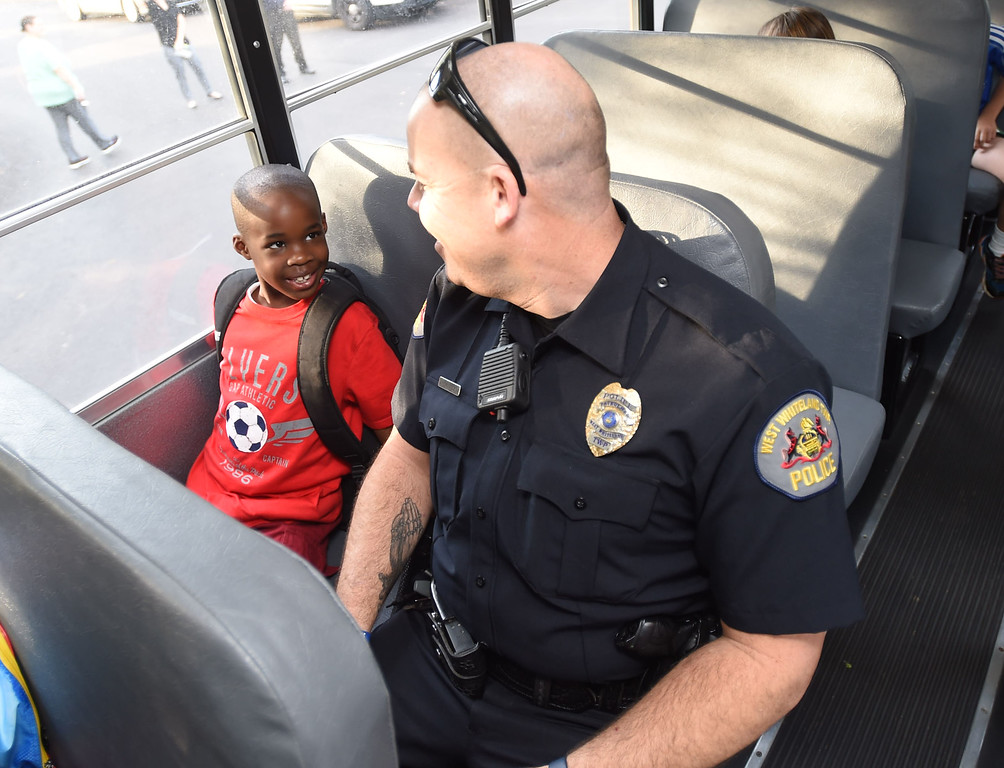 . PETE  BANNAN-DIGITAL FIRST MEDIA         Mary C. Howse Elementary second grade student, Sammuel Morris,7, speaks with West Whiteland Police Detective Jeff McCloskey who rode the school bus Wednesday to speak to the children about school bus safety as part of Operation Safe Stop.  Operation Safe Stop is part of National School Bus Safety Week,  a public awareness and enforcement effort to educate the motoring public that passing a stopped school bus, is dangerous and illegal.