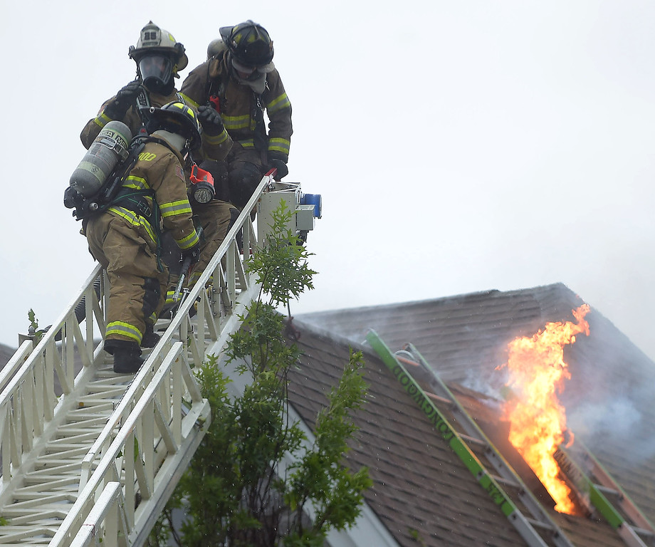 . PETE BANNAN - DIGITAL FIRST MEDIA     Longwood firefighters leave the roof of a house on the 100 block of Osborne Circle, Popcopson after they opened a hole in the roof during a fire Monday afternoon. Nobody was injured in the blaze which went to 3 alarms. The additional crews were required for tanker supply  and manpower.