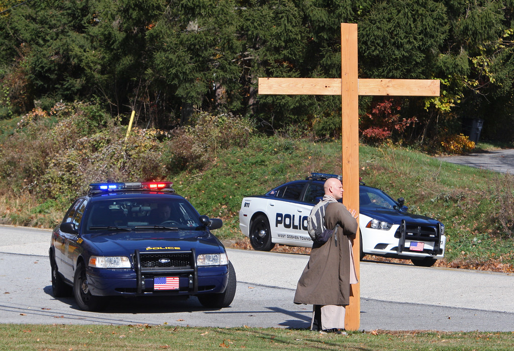 ". Staff Photo by Vinny Tennis  Rev. Tobiah Steinmetz stands with his cross waiting for the police along Pottstown Pike in West Goshen on Monday, Nov. 4, 2013. When asked about how often he is stopped and questioned by police he said, ""I never really thought about it, but I would say about once a week.\'\"" Steinmetz, from Stowe started Cross Walk Ministry after he had a vision of a map of the United States and a man carrying a cross. In 2010 Steinmetz went to the west coast and walked east in 87 days, sometimes walking 20 hours a day. Currently he is walking about 6 miles a day and spreading the gospel as he goes. His card quotes Mark 8:34 \""Take up your cross and follow me.\"" He has teamed up with Caleb Bollinger, from South Carolina and the two are planning to walk to Bollinger\'s home."