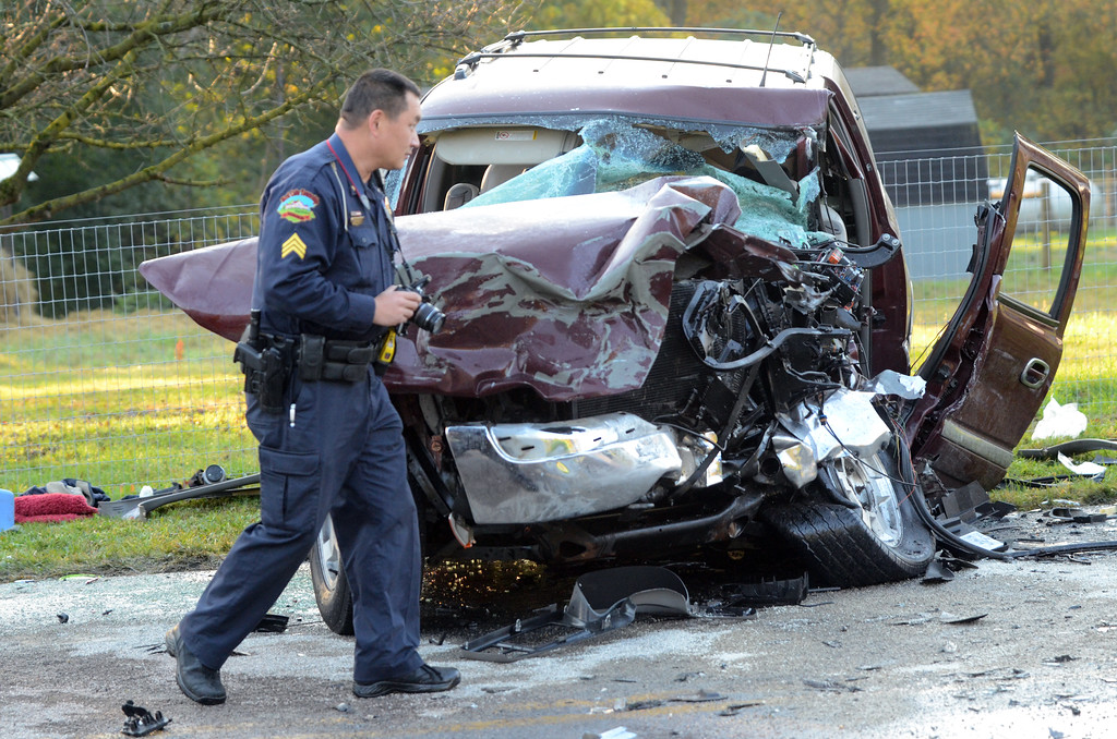 . VINNY TENNIS - Daily Local News  A police officer from West Caln Police Department photographs the scene of an accident on Compass Road, Route 10 just south of Cains Road in West Caln on Tuesday, Oct. 21, 2014. An SUV and a dump truck collided shortly before 7 AM. The roadway was shut for several hours