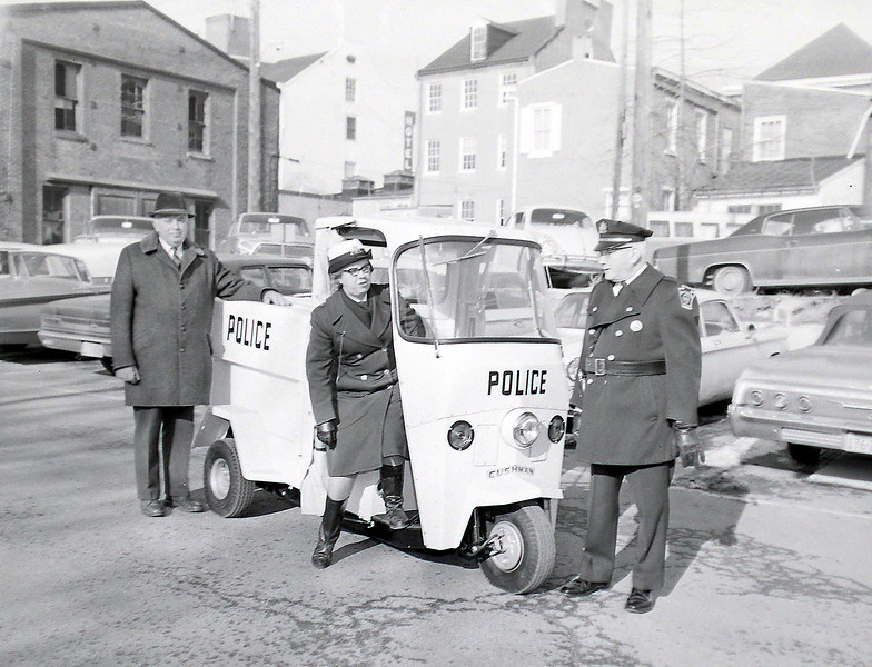 "TEST RUN. Mrs. Joseph Krchnar, the West Chester police department's well-known ""Meter Maid,"" tries the new Cushman three-wheeled vehicle purchased last week, while Mayor Charles H. Andress (left) and PoliceChief George Guss observe.<br /> The $2,000 cycle, equipped with enclosed, heated cab, a two-way radio and a first-aid kit represents an improvement over the department's present motorcycle,whitewall also remain in service.  DLN Staff Photo"