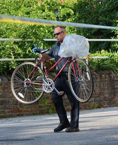 VINNY TENNIS - Daily Local News<br /> <br /> A Coatesville City Police officer collects evidence following an assault in the 300 block of Diamond Street in Coatesville on Thursday, July 16, 2015. The victim was beaten unconscious and airlifted to Paoli Hospital.