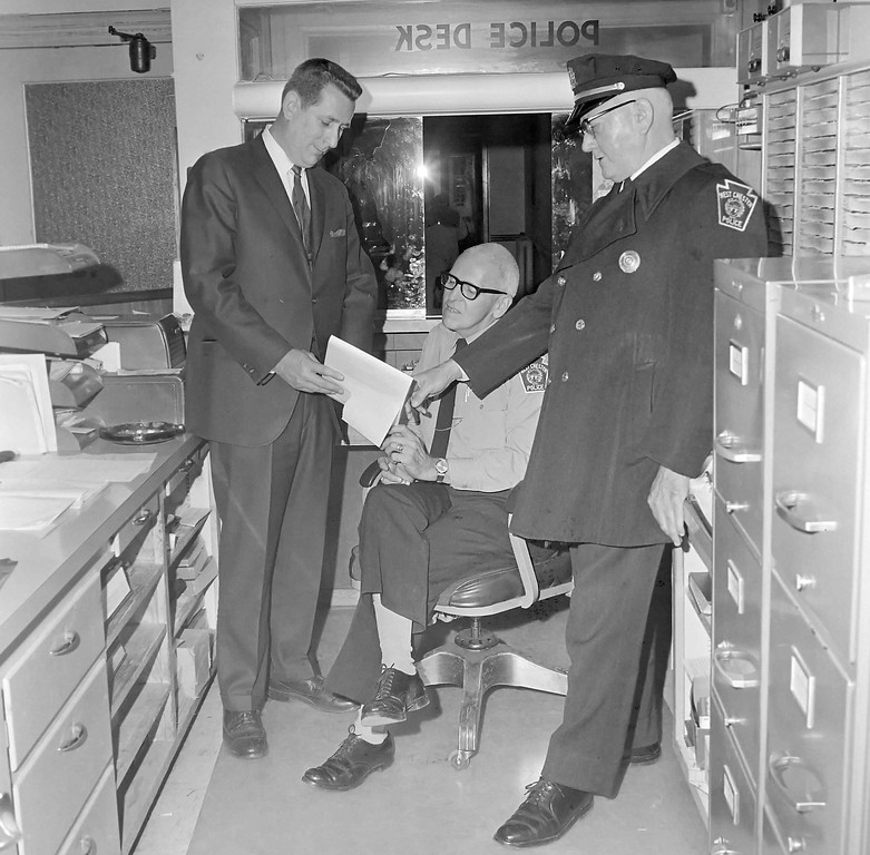 . Change of Command. Retiring West Chester police Chief George H. Guss (right), reviews duties of the past with Chief Chester County Detective THomas G. Frame (left), who will step into the police chief post Jan.1  Looking on is desk Sgt. Linwood Bonner.. Nov. 16, 1968  DAILY LOCAL ARCHIVES