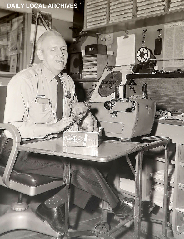 . DAILY LOCAL ARCHIVES - West Chester Sgt. Linwood Bonner at his desk with  a pup found on S. Walnut st. Dec. 2,1962.