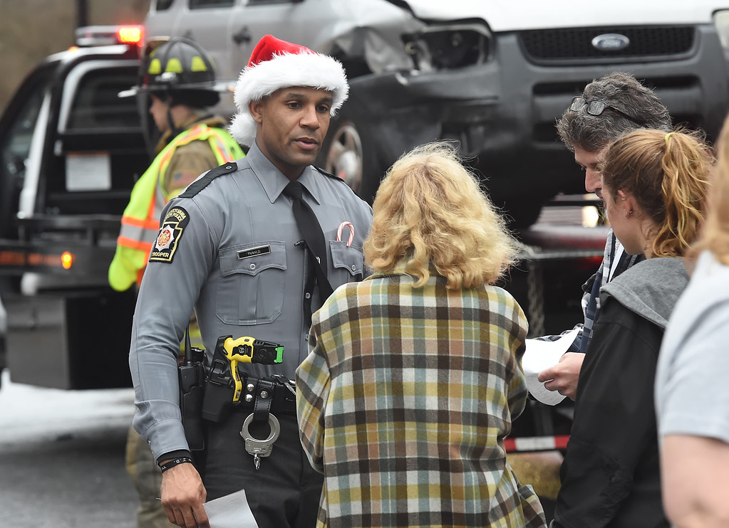 ". VINNY TENNIS - Daily Local News  Santa had a little help on Christmas Eve helping to lighten the mood following a two-car crash on Route 322 and Old Shadyside Road in East Bradford on Thursday, Dec. 24, 2015. Pennsylvania State Police Trooper Rawls wears a Santa hat as he hands paperwork to the individuals involved in the accident, family members were taking pictures with cellphones of the trooper. No one was injured in the accident which brought West Bradford Fire Company and Good Fellowship Ambulance to the scene. PSP requires Troopers to wear their hats as they exit their patrol cars, hopefully Trooper Rawls will stay off the ""Naughty\"" list because he sure deserves to be on the \""Nice\"" list for his actions."