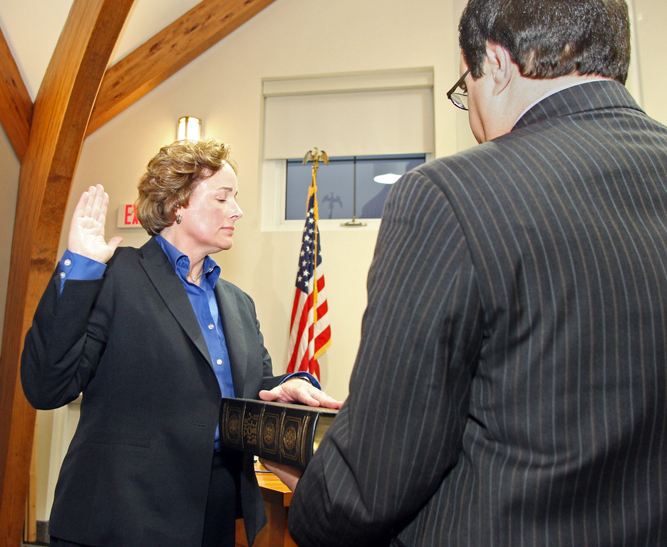 . Staff Photo By Vinny Tennis  Brenda Bernot, left, is sworn in as the new Westtown East Goshen Regional Police Chief by Judge William Kraut at the Westtown Township Building in Westtown on Monday, March 25, 2013. Bernot\'s husband Paul is holding the family Bible for the oath.