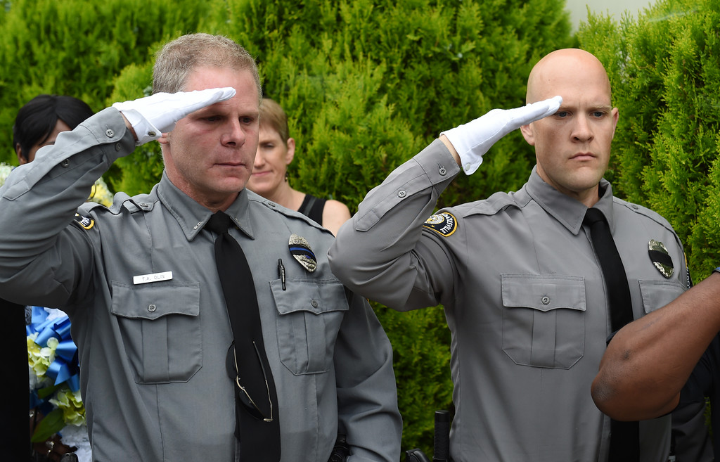 . VINNY TENNIS - Daily Local News  South Coatesville Police officers salute as Officer Arthur Moody is carried to the hearse at Second Baptist Church in Coatesville on Friday, July 17, 2015. Officer Moody passed away suddenly on July 7.