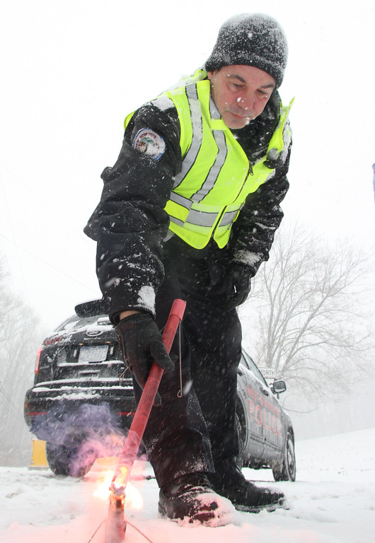 . Staff Photo by Vinny Tennis   West Brandywine Police Officer James Bilski lights another flare at the intersection of Route 82 and Hibernia Road in West Brandywine on Tuesday, Jan. 21, 2014. Route 82 was closed from 340 to 322 for to remove the trucks and for PennDOT plow and salt the roadway.