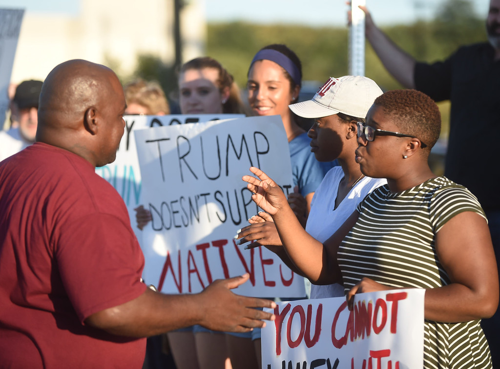 . PETE  BANNAN-DIGITAL FIRST MEDIA    Lorae Bonamy of Chester (right) argues with a vender for selling Trump merchandise out front of the Sun Center before the Trump rally Thurday evening.