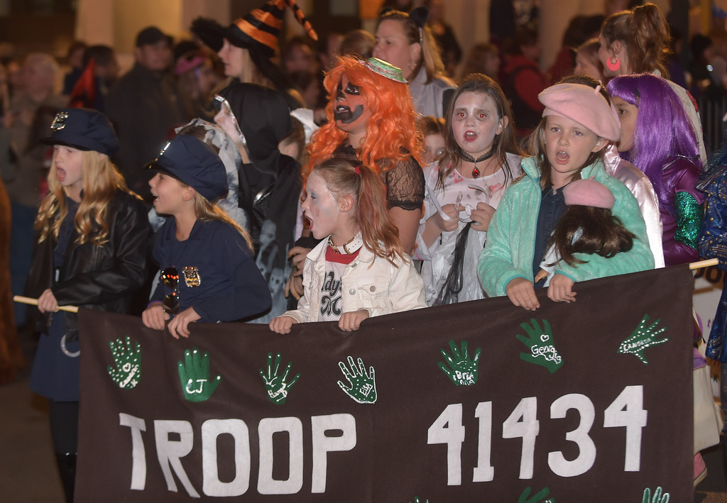 . PETE BANNAN-DIGITAL FIRST MEDIA   	East Goshen GIrl Scout Troop 41434 march in the annual West Chester Halloween parade Wednesday evening.