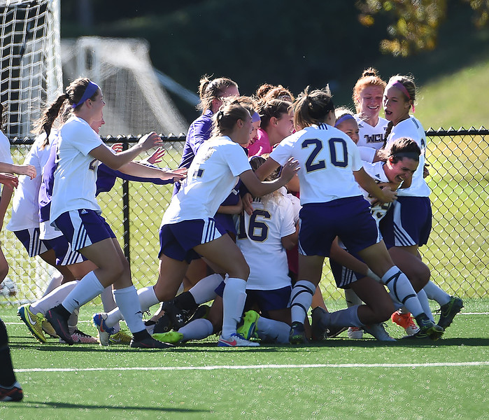 PETE BANNAN-DIGITAL FIRST MEDIA  West Chester University soccer players rush to embrace freshmen, Jenny Bail (right leaning down) after the team beat East Stroudsburg 1-0 on Bail's goal with 45 seconds remaining Tuesday afternoon at Rockwell Field.