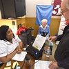PETE BANNAN-DIGITAL FIRST MEDIA  SEPTA official Christian Walker assists Gerri and Charlie McCardell of West Chester  sign up for free bus passes at the West Chester Area Senior Center Vets and Seniors Expo Wednesday.