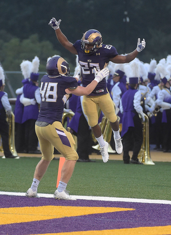. PETE BANNAN  DIGITAL FIRST MEDIA     West Chester University running back (23) Jarel Elder jumps into the arms  tight end Simon Williams after scoing laste in the second quarter of  the Golden Rams 51-9 victory over Bentley Thursday evening at Farrell stadium.