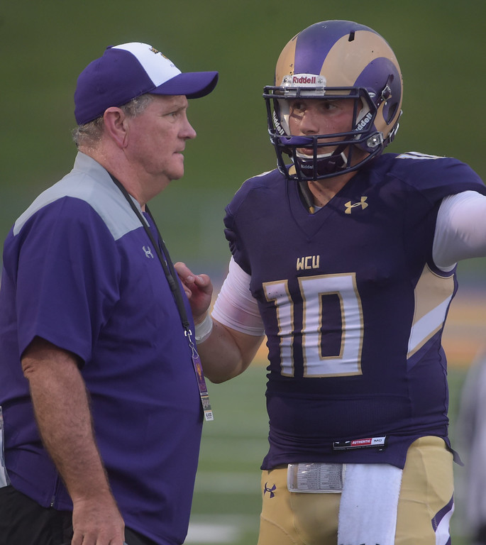 . PETE BANNAN  DIGITAL FIRST MEDIA     West Chester University  head coach Bill Zwaan talks with quarterback Paul Dooley in the first half of the Golden Rams 51-9 victory over Bentley Thursday evening at Farrell stadium.