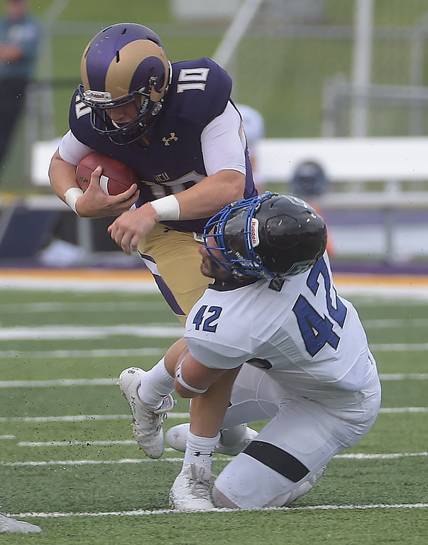. PETE BANNAN  DIGITAL FIRST MEDIA     West Chester University quarterback Paul Dooley runs into Bentley linebacker Rogers Boylan, dislodging his helmet. The Golden Rams went on to a 51-9 victory over Bentley Thursday evening at Farrell stadium.