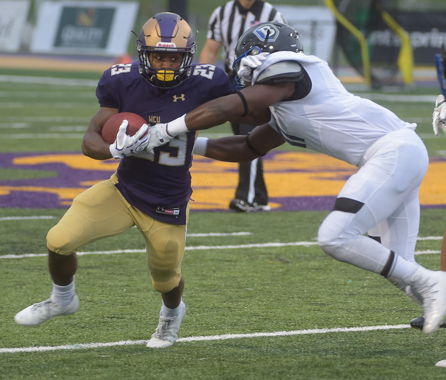 . PETE BANNAN  DIGITAL FIRST MEDIA     West Chester University running back (23) Jarel Elder jtries to avoid Bentley  linebacker Brnadon Brow in the second quarter of  the Golden Rams 51-9 victory over Bentley Thursday evening at Farrell stadium.