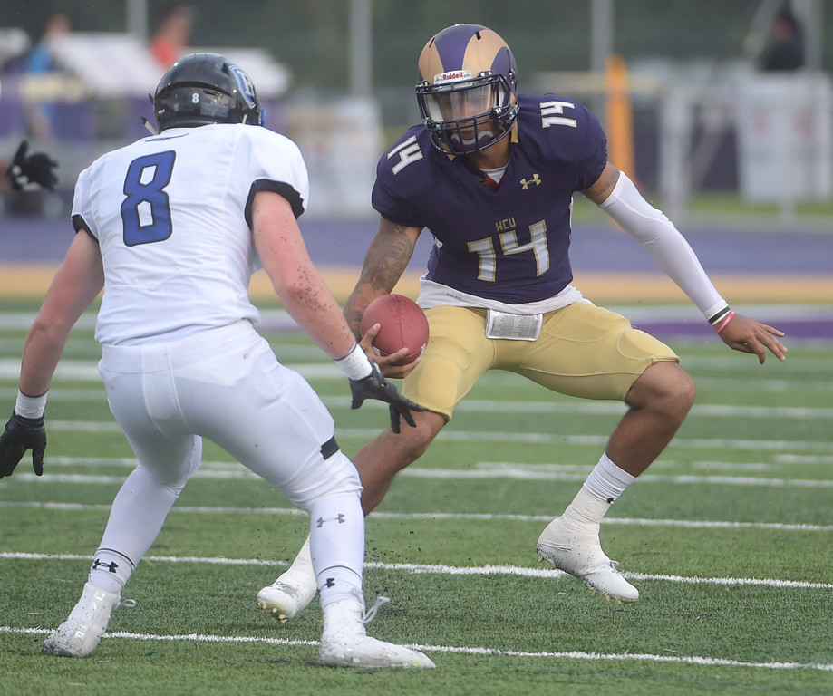 . PETE BANNAN  DIGITAL FIRST MEDIA     West Chester University quarterback AJ Long tries to avoid Bentley linebacker Andrew Carmichaelin the first half for the Golden Rams in their 51-9 victory over Bentley Thursday evening at Farrell stadium.