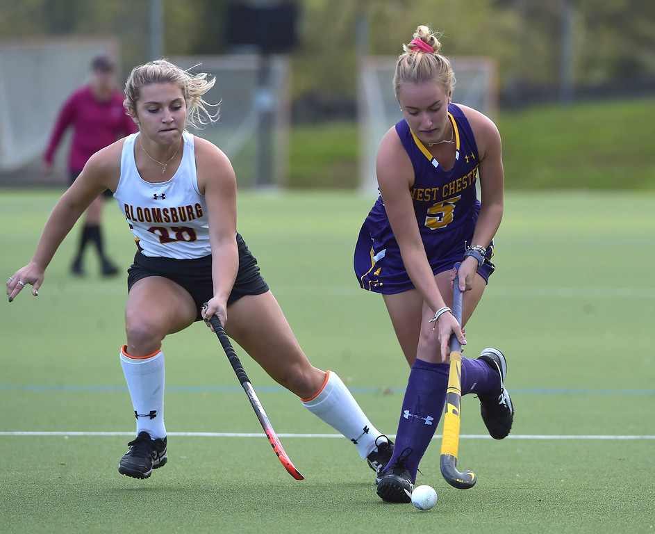 . West Chester University middie (5) EMily Ingalls moves up field as Bloomsburg\'s (28)Arden Morgans defends in the first half Wednesday afternoon at Vonnie Gros field. The Golden Rams defeated Bloomsburg 4-0 to remain in first place in the PSAC.