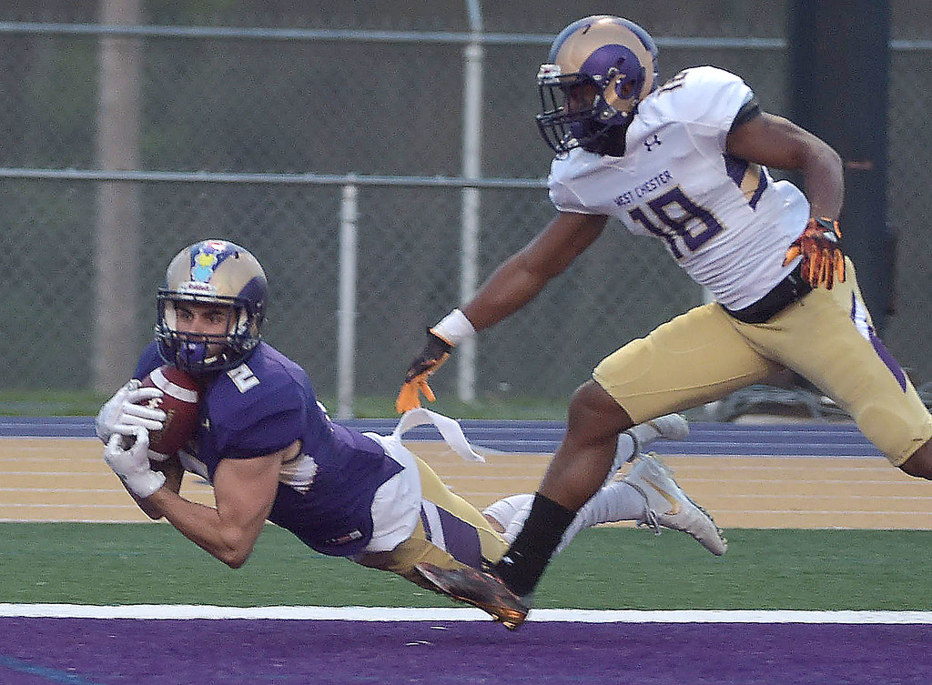 . PETE  BANNAN-DIGITAL FIRST MEDIA        West Chester receiver (2) Lex Rosario  grabs a pass in the endzone as Nydair Rouse defends in the first half of the Purple/Gold scrimmage Friday evening April 27, 2018.