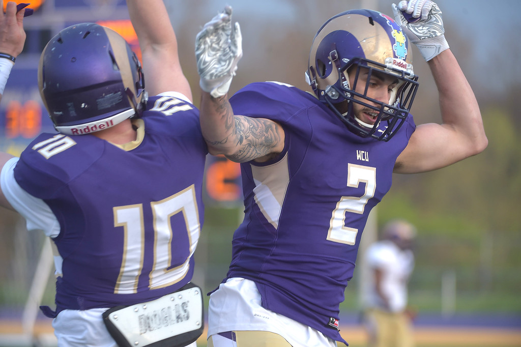 . PETE  BANNAN-DIGITAL FIRST MEDIA        West Chester quarterback Paul Dooley and receiver (2) Lex Rosario celebrate their first half touchdown in the Purple/Gold scrimmage Friday evening April 27, 2018.