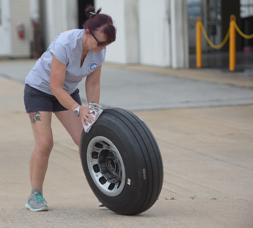 . PETE BANNAN  DIGITAL FIRST MEDIA    Amanda Dean rolls a spare P-51 Mustang wheel at Chester County  G.O. Carlson airport Monday as part of the Wings of Freedom Tour.