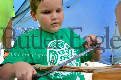 Liam Cubarney, a 10-year-old from Jackson Township, carves a walking stick at the tent hosted by the North Country Trail Association's Wampum Chapter.