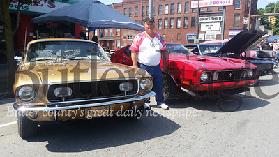 John Malinski, president of the Butler Rod Fathers, poses with two of the five Ford Mustangs he showed on Sunday at the Cruise-A-Palooza on Main Street. Malinski said he will meet with the Rod Fathers members as well as Butler Mayor Ben Smith regarding holding the event downtown again next year.