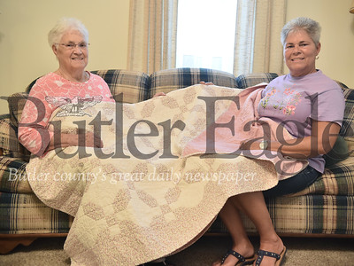 54377 Pat Taggert is handing down a quilt to her daughter Joan Davenport at her home in Butler