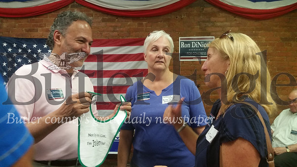 Ron DiNicola, the Democratic candidate who will try to unseat US Rep. Mike Kelly in November for the 3rd district, holds a bib from the Butler Italian Festival bought by his canvasser Lynn Spadine-Taylor, right, of Zelienople. DiNicola, of Erie, held the grand opening on Sunday of his new office at 306 N. Main St. Also pictured is Catherine Lalond, the chairwoman of the Butler County Democratic Committee.