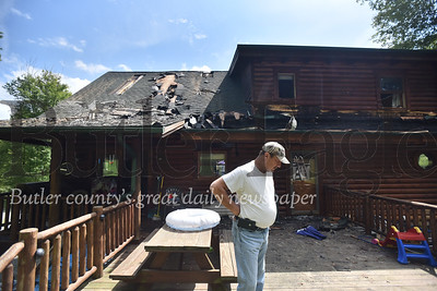 67300 John Manson and his family are picking up the pieces after fire Wednesday night damaged their log home on Spring Run Road in Center Twp