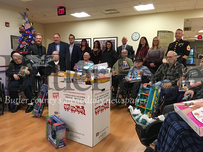 Members of Berkshire Hathaway's Chuck Swidzinski's team, rear, accept toys donated by residents of VA Butler Healthcare community living center for the Toys for Tots program.