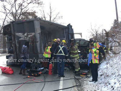 Unionville volunteer firefighters and a Butler Ambulance Service crew team up to help rescue a woman trapped inside her sport utility vehicle that collided with a dump truck about 10 a.m. Friday on Route 308 in Center Township. 3 Column Photo.