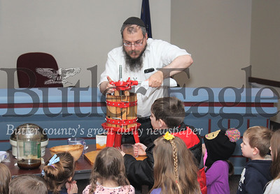 Harold Aughton/Special to the Eagle: Rabbi Choni Friedman of Green Field demonstrates how to press olives to the children attending the Hanukkah celebration at the Cranberry Twp. Municipal building Sunday evening.