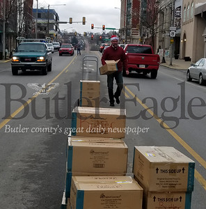 Mike Robb, executive director for CCR, on his way to grab a fresh box of cookies to hand out on Christmas Eve along Main Street in Butler.  NATHAN BOTTIGER/BUTLER EAGLE
