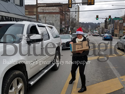 Jodi Yute, CCR prevention education specialist, hands out cookies to passing cars on Christmas Eve along Main Street in Butler. NATHAN BOTTIGER/BUTLER EAGLE