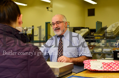 Jack Hutchinson, the lead clerk at Butler's post office, helps a customer send a package on Dec. 26, 2018. Tanner Cole/Butler Eagle