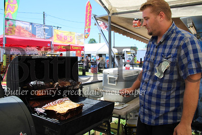Edward Kimmons, 28, of Marion, Ohio, tends to the smoker, which cooked brisket, pork and ribs, at the Big Butler Fair on July 7, 2018