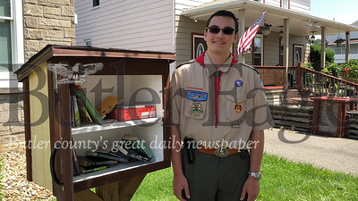 John Volkar, a members of Mars Scout Troop 400, stands next to one of the four Little Free Library boxes he installed as part of an Eagle Scout project.