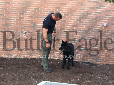 Keith Ware of the Monroe County (W.Va.) Sheriff's Office takes dog in training, Barrett, out for a walk around the Butler County Prison.