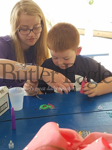 Caitlin Moss (left) helps Silas Bouse with his plastic-glass painting at the South Hills Playground, as part of the Summer Food & Fun Program, sponsored by the Greater Pittsburgh Food Bank.