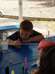 Silas Bouse works on his plastic-glass painting at the South Hills Playground, as part of the Summer Food & Fun Program, sponsored by the Greater Pittsburgh Food Bank.