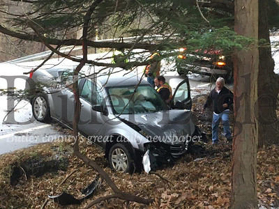 A Butler Ambulance Service crew tends to a woman after she lost control of her car on icy Route 308 in Center Township and struck a ditch about 10:20 a.m. Thursday.